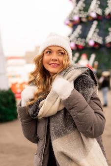Retrato de rua de mulher jovem e bonita sorridente na festiva feira de natal. senhora vestindo roupas de malha elegantes clássicas de inverno. modelo olhando para a câmera. efeito de neve mágica. fechar-se