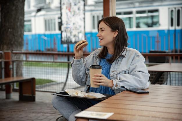 Retrato de rua de uma jovem alegre, desfrutando de um hambúrguer e café lá fora.