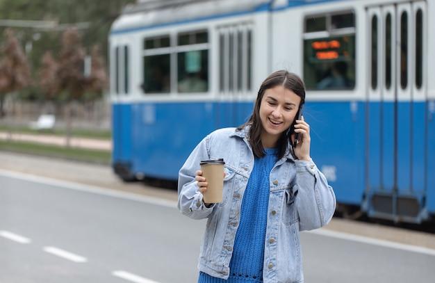Retrato de rua de uma jovem alegre, falando ao telefone com café na mão.