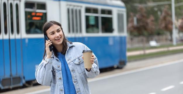 Retrato de rua de uma jovem alegre falando ao telefone com café na mão