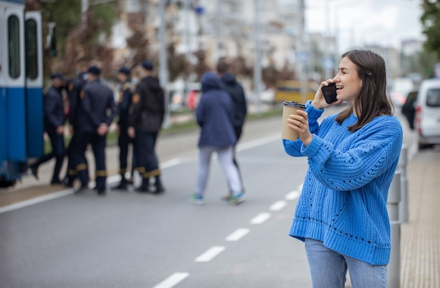 Retrato de rua de uma jovem falando ao telefone na cidade perto da estrada.