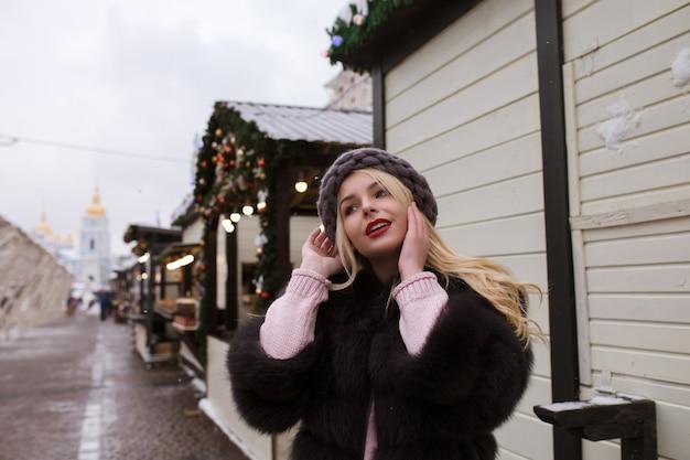 Retrato de rua de uma jovem glamourosa com elegante chapéu de malha e casaco de pele, posando na feira de natal. espaço para texto