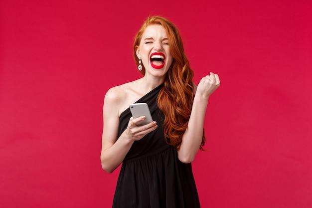 Retrato de ruiva bem-sucedida e satisfeita, ganhando, receba ótimas notícias por mensagem, bomba de presente como campeão, grite sim, ela fez isso, triunfando em vestido preto elegante, parede vermelha