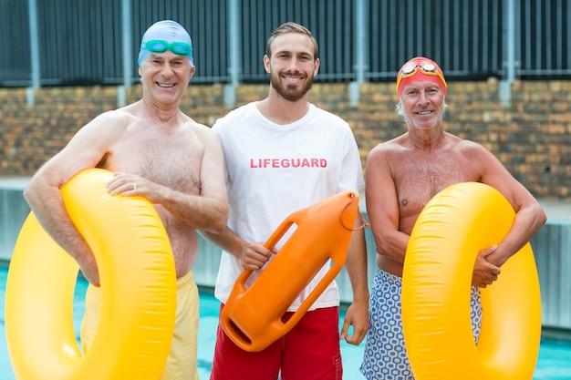 Retrato de salva-vidas com nadadores sênior à beira da piscina