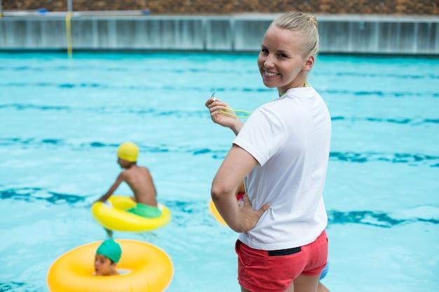 Retrato de salva-vidas confiante segurando o apito à beira da piscina