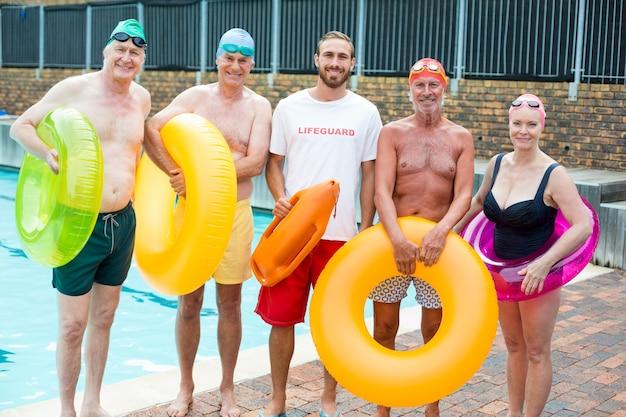 Retrato de salva-vidas masculino com nadadores sênior à beira da piscina