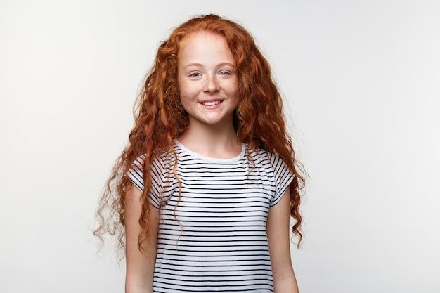 Retrato de sardas fofas positivas menina com cabelo ruivo, fica sobre uma parede branca e amplamente sorrindo, parece feliz e contente.