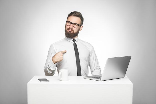 Retrato de satisfeito confiante sorridente jovem gerente barbudo de camisa branca e gravata preta está sentado no escritório está orgulhoso de si mesmo por objetivos alcançados no trabalho. foto de estúdio, interna, isolada