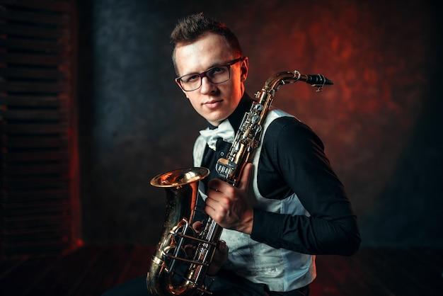 Retrato de saxofonista masculino com saxofone, homem de jazz com sax.
