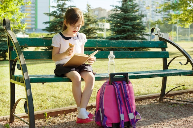 Retrato, de, schoolgirl, livro leitura, comendo sorvete