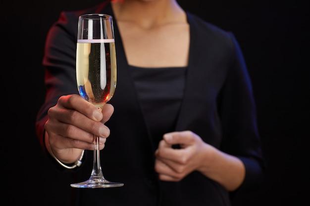 Retrato de seção intermediária de uma mulher elegante e irreconhecível segurando uma taça de champanhe em pé contra um fundo preto na festa, copie o espaço
