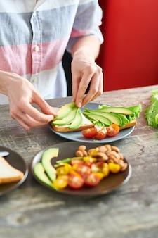 Retrato de seção mestra de jovem irreconhecível que cozinha o café da manhã saudável na manhã