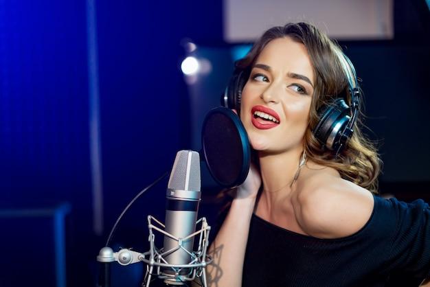 Retrato de sedutora menina feliz linda jovem cantando com microfone