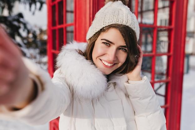 Retrato de selfie alegre linda mulher com chapéu de lã branco aproveitando a manhã ensolarada de inverno na cabine telefônica vermelha