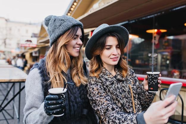 Retrato de selfie de alegres mulheres na moda, se divertindo na rua ensolarada da cidade. look estiloso, se divertindo, viajando com amigos, sorrindo, expressando verdadeiras emoções positivas.