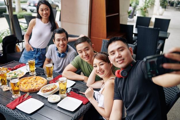 Retrato de selfie de amigos em restaurante