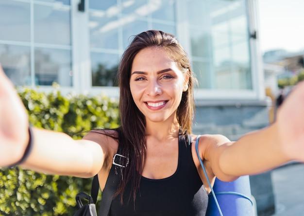 Retrato de selfie jovem alegre em forma de mulher em top esportivo com bolsa nos ombros sorrindo ao ar livre