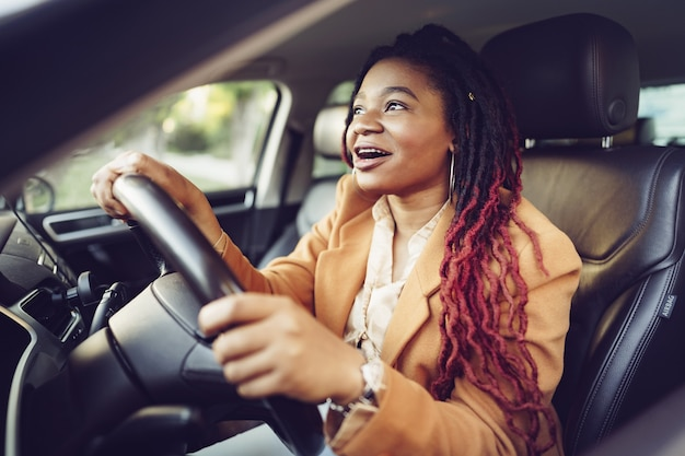 Retrato de senhora afro-americana positiva dentro do carro