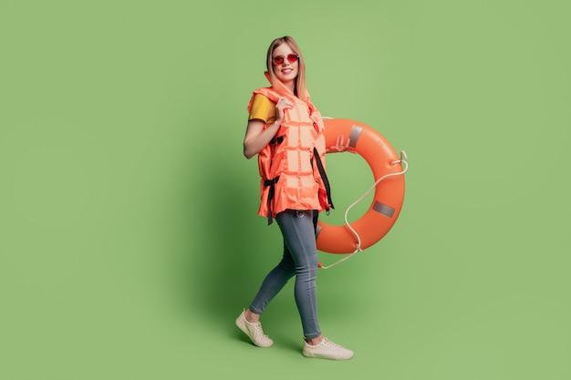 Retrato de senhora andar segurar círculo inflável usar óculos de sol colete laranja sapatos jeans sobre fundo verde