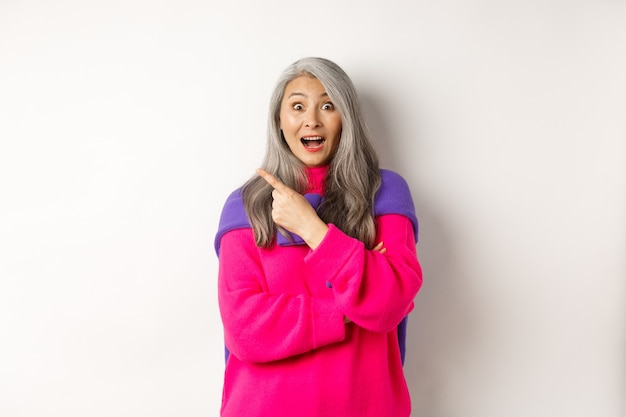 Retrato de senhora asiática impressionada verificando a oferta promocional, apontando para o canto superior esquerdo e olhando para a câmera espantada, em pé no moderno suéter rosa sobre fundo branco.