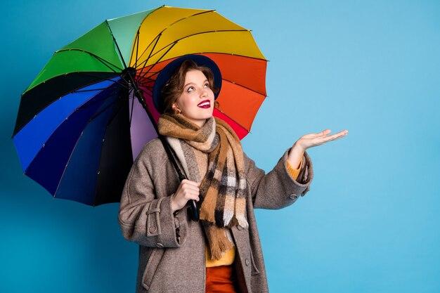 Retrato de senhora bonita viajante segurar guarda-sol colorido caminhada rua verificar o braço se a chuva parou de usar elegante casual longo cinza casaco calças jumper chapéu xadrez cachecol.