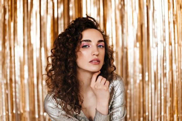 Retrato de senhora com linda maquiagem olha para a câmera sobre fundo dourado