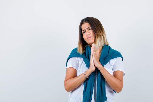 Retrato de senhora com suéter amarrado, mostrando as mãos postas em um gesto de súplica em camiseta branca e vista frontal sombria