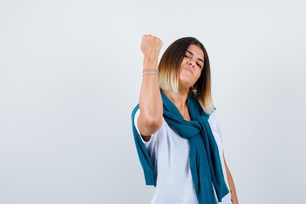 Retrato de senhora com suéter amarrado mostrando o gesto do vencedor em uma camiseta branca e olhando com sorte a vista frontal