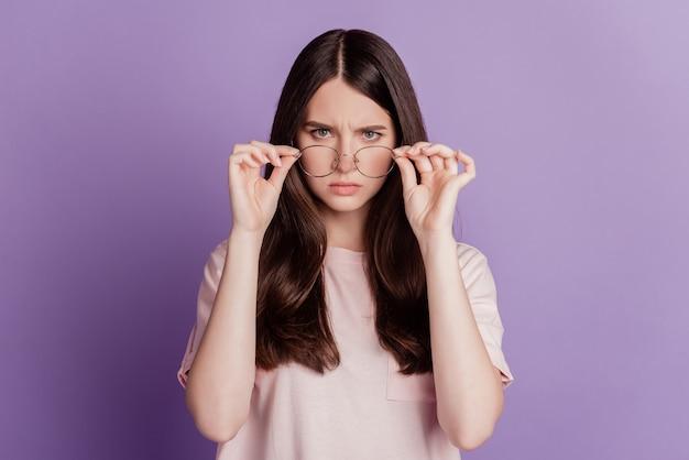 Retrato de senhora confiante em especificações isoladas em fundo violeta