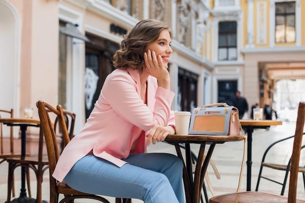 Retrato de senhora elegante e sorridente, sentada à mesa, bebendo café na tendência de estilo de verão de jaqueta rosa, bolsa azul, acessórios, estilo de rua, moda feminina