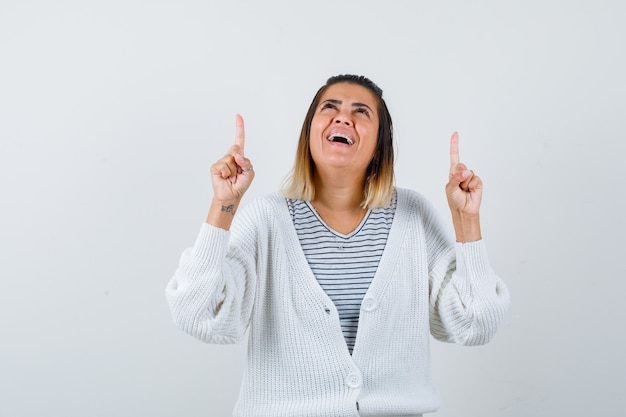 Retrato de senhora encantadora apontando para cima, olhando para cima em camiseta, casaco de lã e parecendo feliz