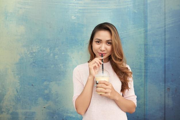Retrato de senhora encantadora, desfrutando de milkshake, olhando para a câmera