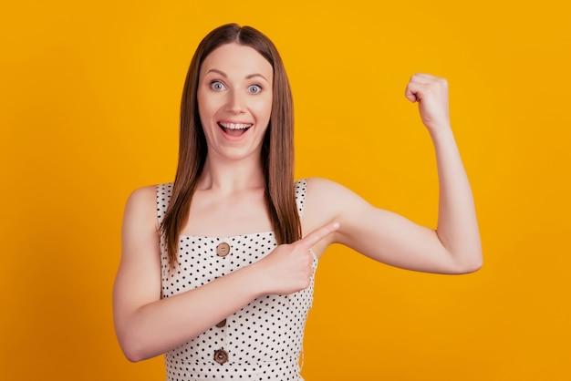 Retrato de senhora forte e animada, levantando a mão, mostrando o dedo direto do bíceps no fundo amarelo