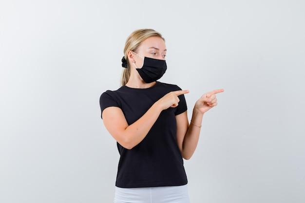Retrato de senhora loira apontando para a direita em camiseta preta, máscara preta isolada