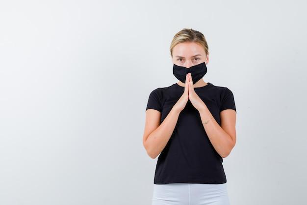 Retrato de senhora loira de mãos dadas em gesto de oração em camiseta preta isolada