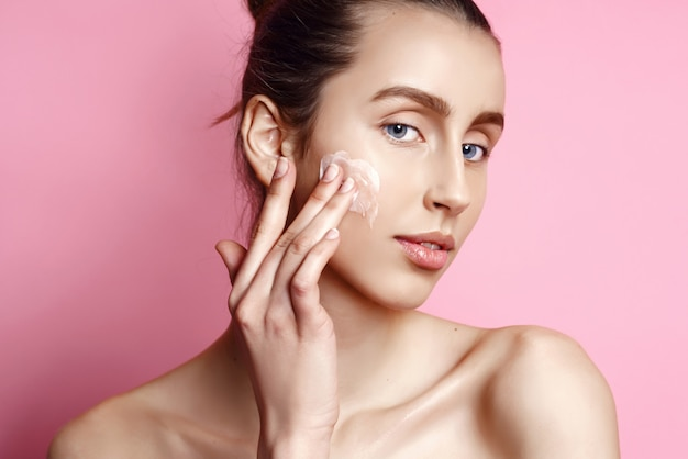 Retrato de senhora modelo linda com maquiagem natural, aplicar creme no rosto. isolado em rosa