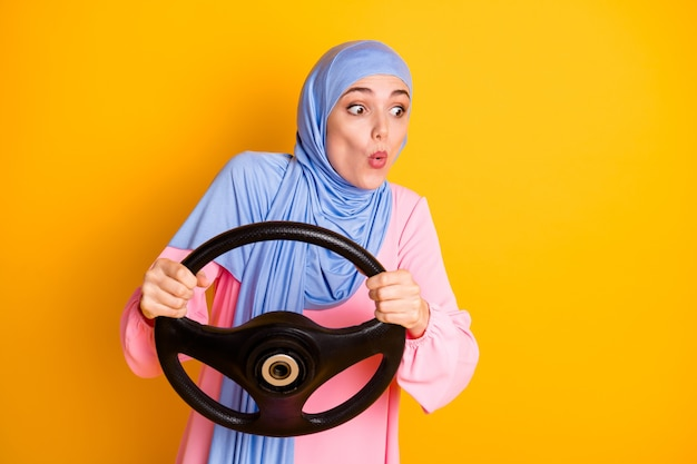 Retrato de senhora muslimah muito atenciosa usando hijab dirigindo carro invisível beicinho lábios caminho estrada rota isolada em fundo de cor amarela brilhante