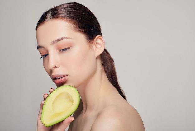 Retrato de senhora nua de cabelos castanho calmo com abacate