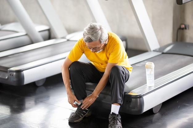 Retrato de sênior com óculos, fazendo exercícios no ginásio de fitness.