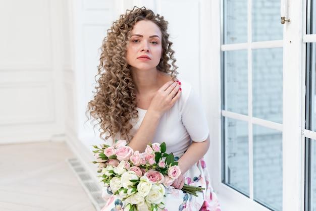 Retrato, de, sensual, loiro, menina curly, senta-se, logo, a, janela, e, segura, um, buquê rosas