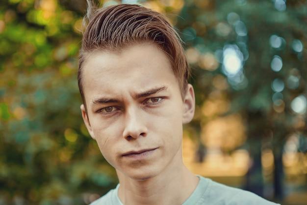 Retrato de sério jovem atraente branco 23 anos de idade durante uma caminhada em parque público.