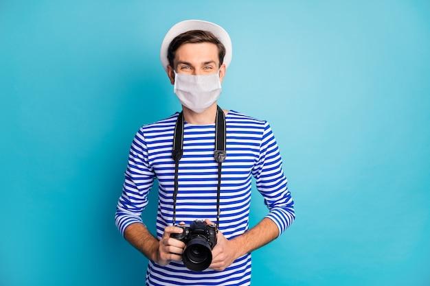 Retrato de seu viajante atraente usando máscara de segurança segurando na mão cam pandemia influenza descontaminação medidas preventivas mers china wuhan isolado fundo de cor azul