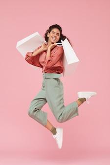 Retrato de shopaholic feliz curtindo suas compras, ela pulando com sacolas de compras contra o fundo rosa