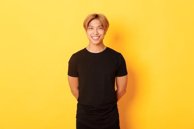 Retrato de simpático rapaz asiático com cabelo loiro, sorrindo educadamente, de mãos dadas atrás das costas, em pé na parede amarela