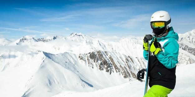 Retrato de snowboarder em paisagem de altas montanhas nevadas
