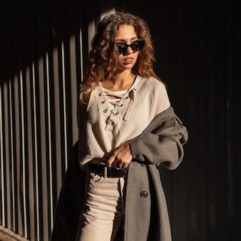 Retrato de sol de uma bela jovem com cabelos cacheados em elegantes roupas urbanas com um casaco da moda e blusa de tricô em óculos de sol na rua