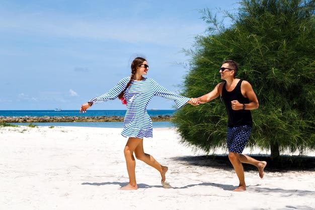 Retrato de sol de verão de lindo casal, tendo férias românticas na ilha tropical. correndo e enlouquecendo juntos.