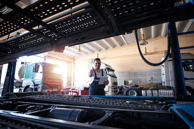 Retrato de soldado de caminhão sorridente positivo parado por um veículo de caminhão na oficina.