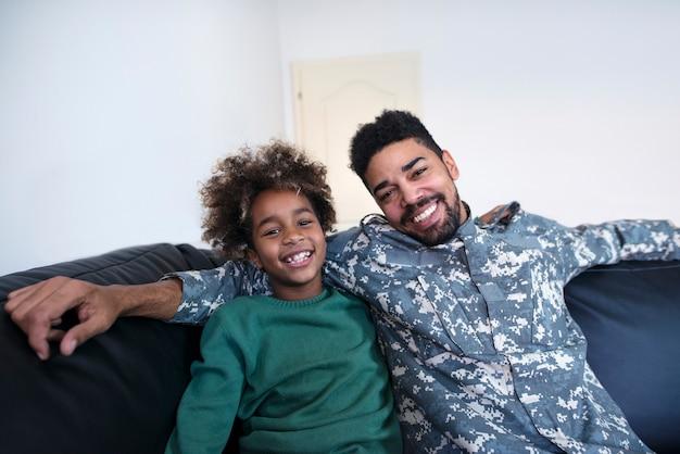 Retrato de soldado em uniforme militar com a filha em casa