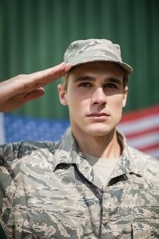 Retrato de soldado militar dando continência em campo de treinamento